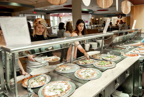 Students picking out pizza from a buffet in a campus dining hall.